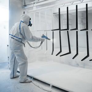 man in spray suit applying white powder coating